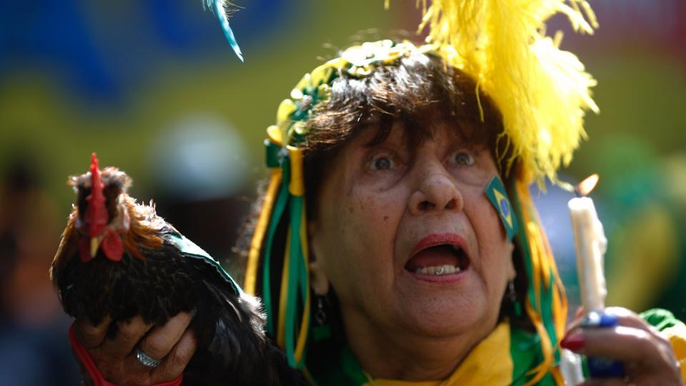 A fan of Brazil holds a hen as she watches the World Cup match between Brazil and Mexico on a big screen in Rio de Janeiro. (AFP)