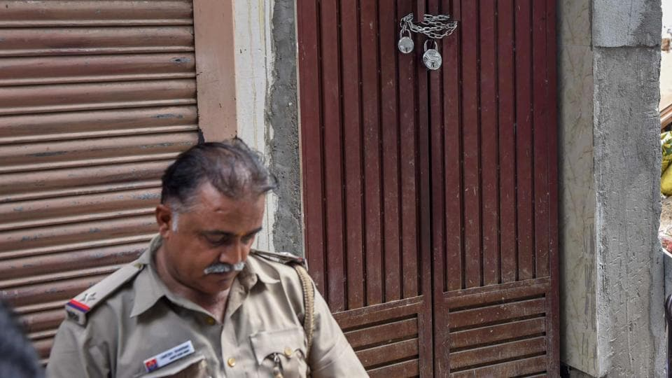 A policeman guards outside the house of Bhatia family in north Delhi's Burari on Tuesday, July 3, 2018. Eleven members of the family were found dead on July 1, 2018.