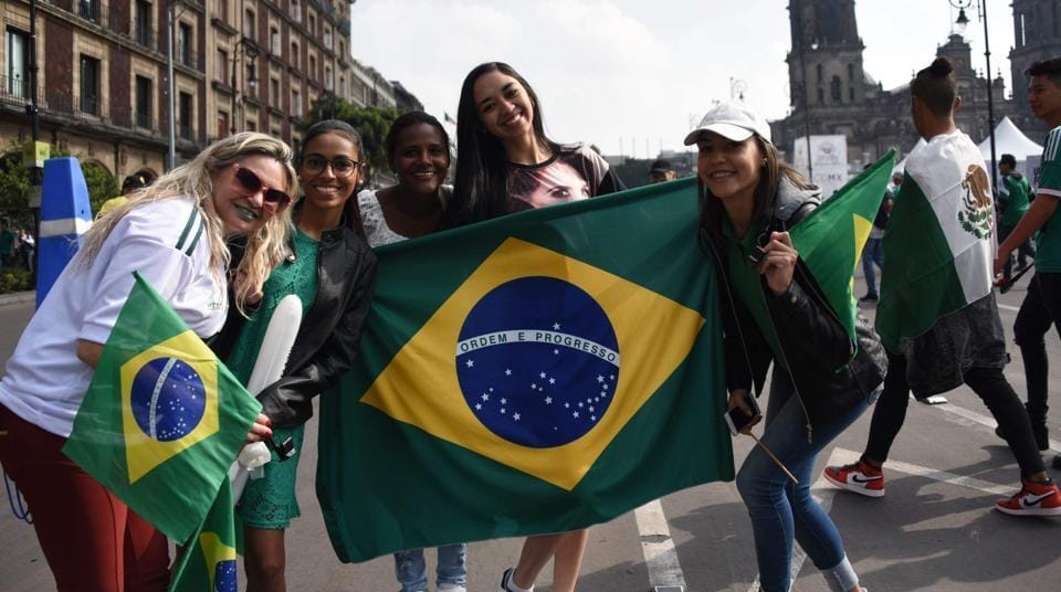Fans of Mexico and Brazil pose for pictures as they watch the World Cup football match between their national teams during a public event at Zocalo Square in Mexico City. (AFP)