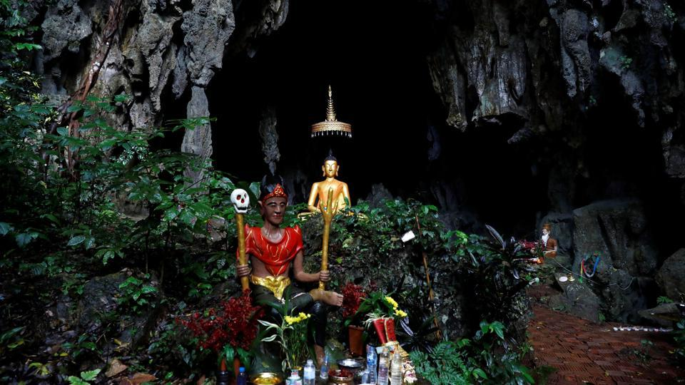 A spirit and Buddha statue are seen in front of the Tham Luang cave complex. Aged between 11 and 16, twelve soccer players and their 25-year-old coach went missing on June 23, after they set out to explore the caves in a forest park. Now that the group has been found, the next step is determining how to get them safely out of the partly flooded cave in northern Thailand. (Soe Zeya Tun / REUTERS)