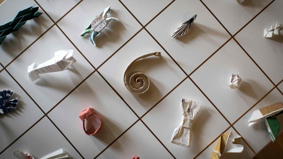 """A collection of origami made from chopstick sleeves maintained by Yuki Tatsumi in Kameoka, Kyoto. Tatsumi was waiting tables at a pub when something on the table caught his eye -- a chopstick wrapper folded and fiddled into an abstract shape. It was the catalyst for a collection that now includes 15,000 pieces of found """"origami art"""" made by restaurant customers from paper sleeves that cover chopsticks. (Harumi Ozawa / AFP)"""