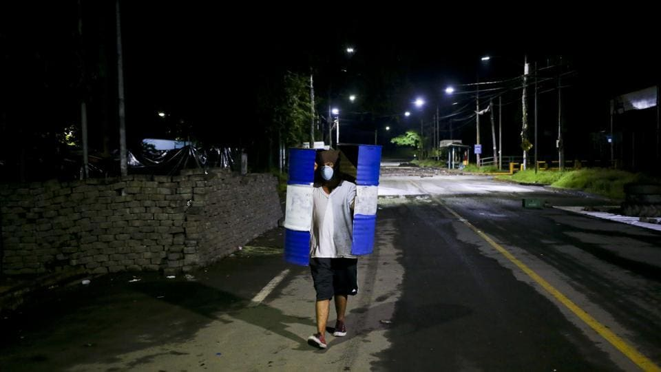 A student walks outside the school carrying a metal trash barrel, cut in half and used as a shield. An ambulance arrived, but students sent it away because they did not trust that he would receive care at a public hospital and feared it might carry attackers. Students took Chavarria to a private hospital where he later died. (Esteban Felix / AP)