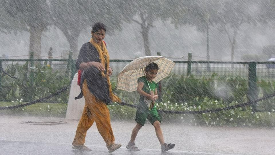 A girl walks under an umbrella with her mother during sudden rain, at Rajpath, in New Delhi.