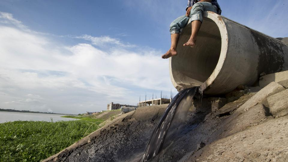 """A Bangladeshi man sits on a concrete pipe, as tannery waste empties out into the Daleshwari River in Savar, Bangladesh. """"It's killing the river. The colour of the water has changed,"""" Abdus Shakur, a local resident who works as a day labourer, told The Associated Press last week. """"I have been living here for decades and the condition of the river has changed dramatically over the last year."""" (A.M Ahad / AP)"""