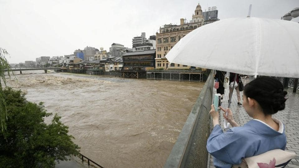 A kimono-clad woman using a smartphone takes photos of swollen Kamo River, caused by a heavy rain, from Shijo Bridge in Kyoto, western Japan, on Thursday.