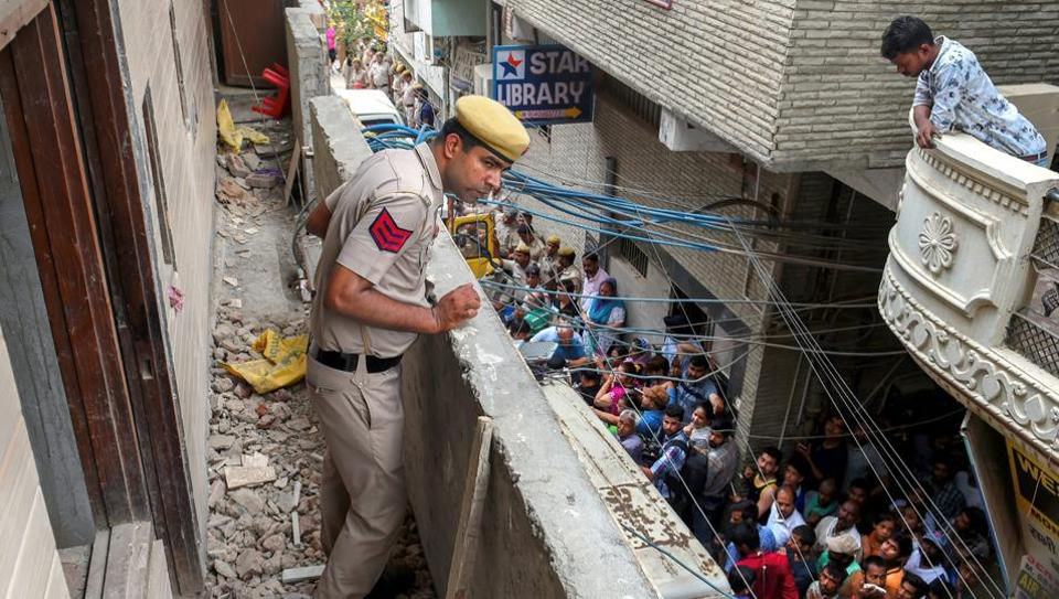 A police man stands in the balcony of the house, where 11 members of a family were found hanging from an iron grill, in Burari area of New Delhi.