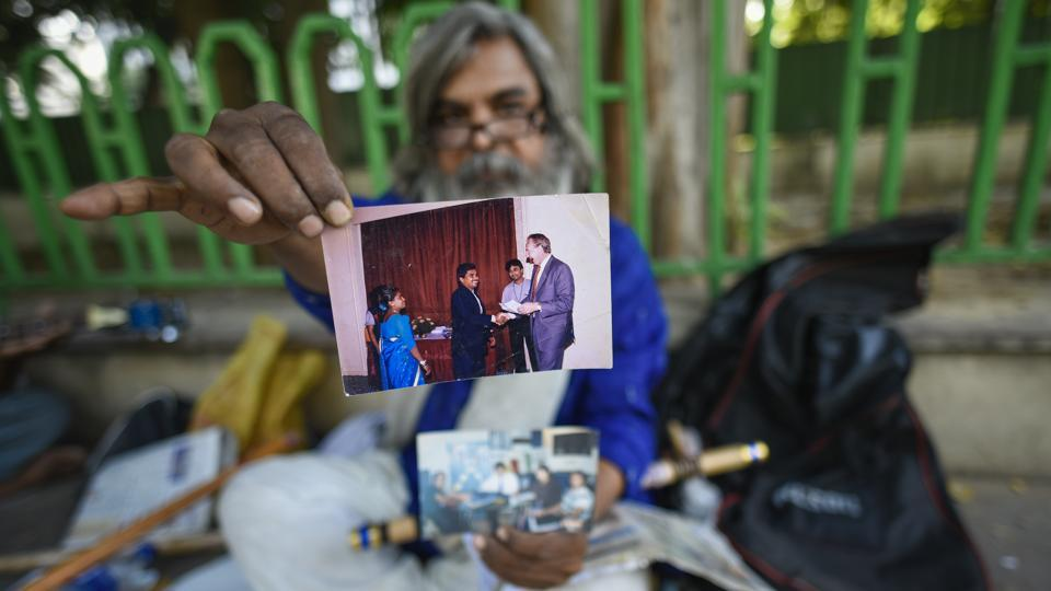 "Rao shows an old photograph of him receiving his Civil Engineering degree. ""This is my institute,"" he said, sitting under the shade of a tree by the footpath. He recalls his professional life as an angry one, in contrast to his days now, free from anguish and spent in temples, ashrams or the Andhra Bhawan's grounds. (Burhaan Kinu / HT Photo)"