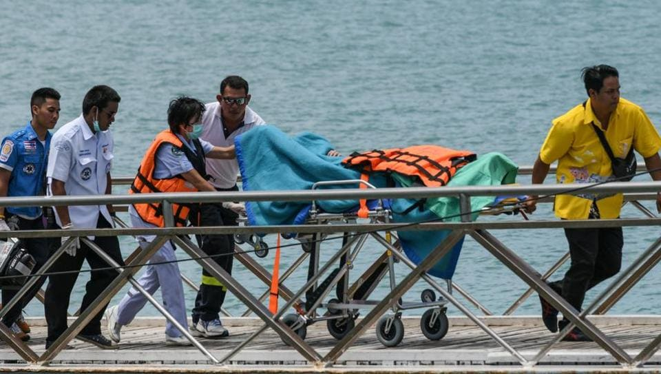Thai rescue personnel move a passenger on a stretcher at Chalong pier in Phuket on July 6, 2018.
