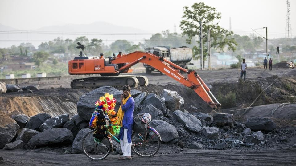 A festoon seller sits on a bicycle as an excavator operates at the Tori Siding. The Railways earn revenue of Rs 100 crore for every 1 MT of coal transported to about 500 km. Even if 100 MT is to be transported by Tori-Shivpur, this railway line is expected to generate about Rs 10,000 crore per annum. (Prashanth Vishwanathan / Bloomberg)
