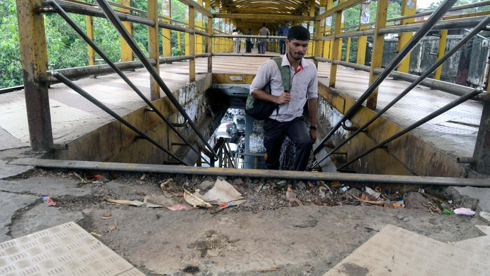 A pedestrian walks on the dilapidated Kalyan skywalk on Friday. The tiles on the skywalk have come off, while the shed has gone missing at one end of the skywalk.