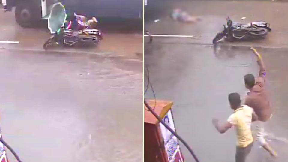 The two-wheeler can be seen slipping as it goes over a pothole on the waterlogged road and both the rider and pillion fall to their right.