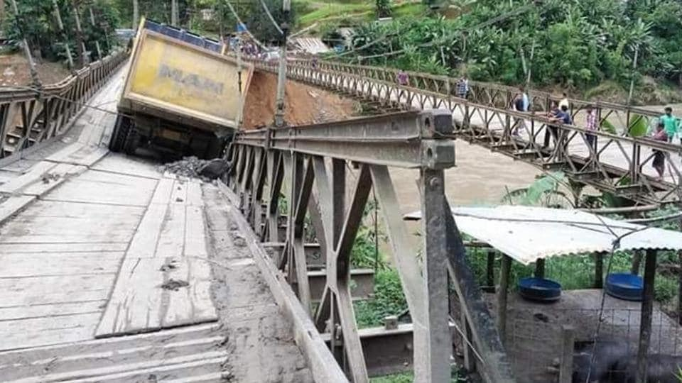 The bridge over Barak River along the Imphal-Jiribam sector of NH 37 was damaged when a loaded truck was passing on Sunday morning while a stretch of around 100 metre of the busy Kohima-Dimapur sector of NH 29 near Nagaland's state capital sank in the intervening night of Saturday and Sunday following incessant rain in the last few days. (HT Photo)