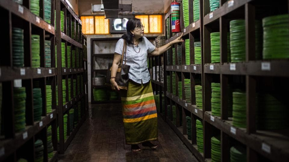 """Actor Grace Swe Zin Htaik views old films at the state archive in Yangon. The survival of Myanmar's earliest film around, """"Mya Ga Naing"""" (The Emerald Jungle), is perhaps as unlikely a feat as its lead role's triumph over pythons and bandits with his bare hands. The country's once flourishing film scene was hit with the military junta's arrival in 1962 that brought stringent censorship during a 50-year reign. (Phyo Hein Kyaw / AFP)"""