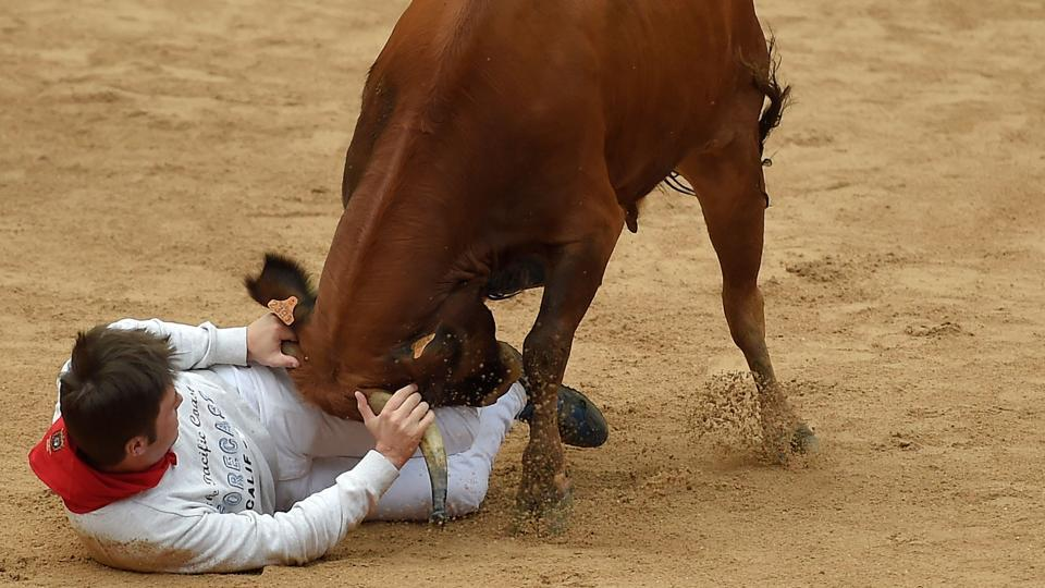 """A reveller is tossed by a heifer bull during festivities in the bullring on the first day of Pamplona's famed San Fermin running of the bulls festival with a traditional firework known as the """"Chupinazo."""" (Jose Jordan / AFP)"""