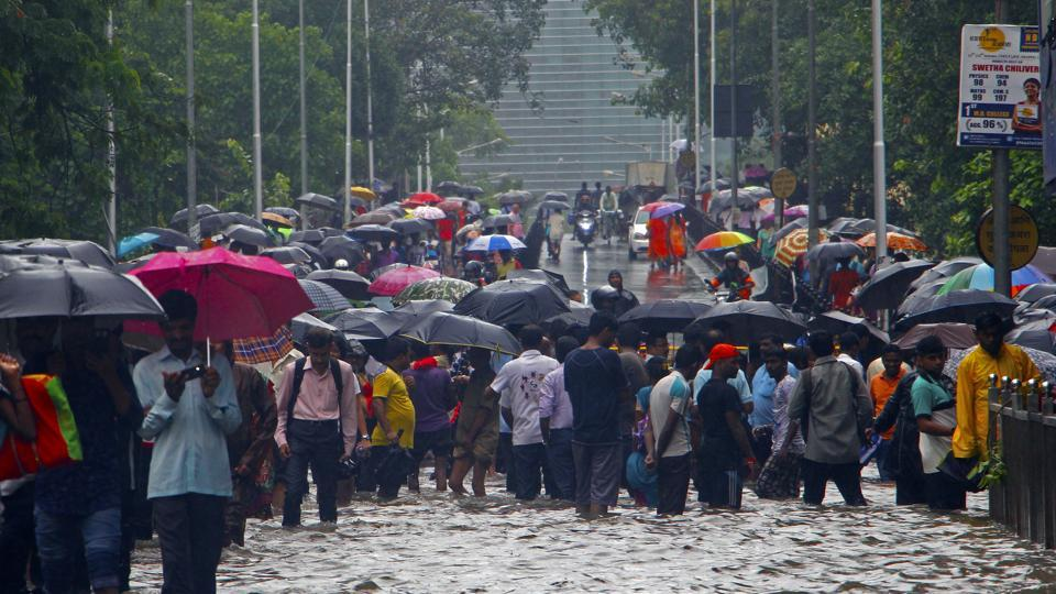 People wade through waterlogged road near Parel bridge in Mumbai, on Tuesday, July 10, 2018.