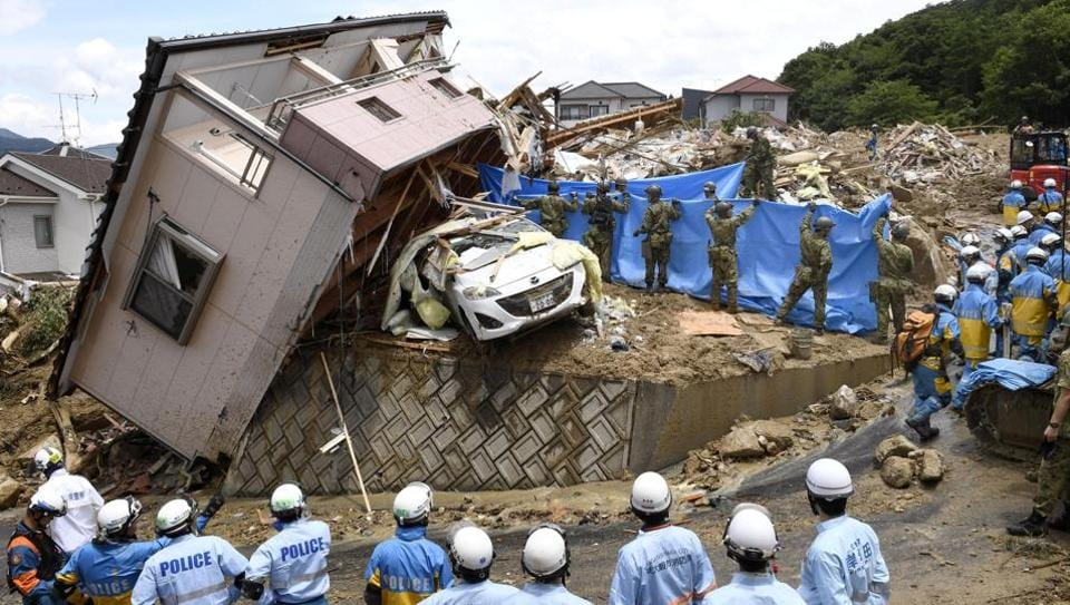 Rescue workers look for missing people in a house damaged by heavy rain in Kumano town, Hiroshima Prefecture, Japan on July 9, 2018. Rescuers combed through mud-covered hillsides and near riverbanks Tuesday to look for dozens of people still missing after days of heavy rains caused flooding and mudslides in southwestern Japan, where the death toll has risen to 141. (Kyodo via REUTERS)