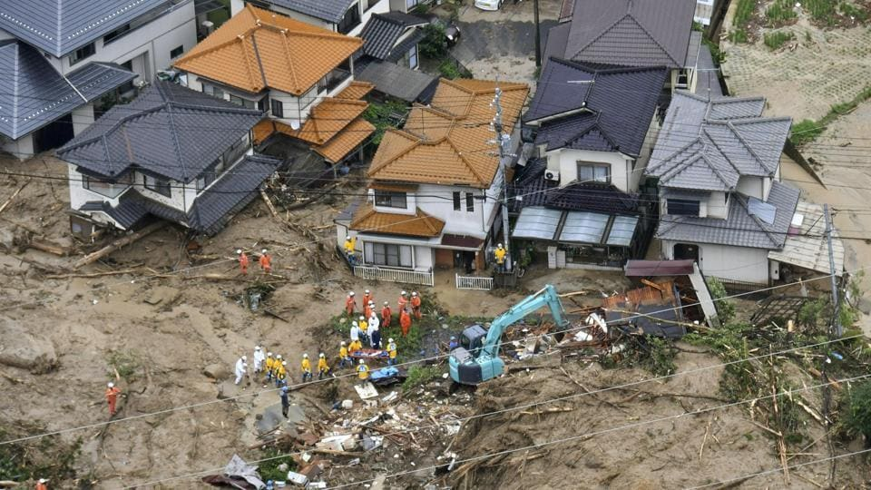 Rescue workers are seen next to houses damaged by a landslide following heavy rain in Hiroshima. In the Mabi district of Kurashiki, the water left behind a fine yellow silt that has transformed the area into moonscape. (Kyodo via REUTERS)
