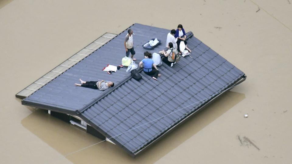 An aerial view shows local residents seen on the roof of submerged house in Kurashiki. Some homes were smashed, while others were tilting precariously. Rivers overflowed, turning towns into lakes and leaving dozens of people stranded on rooftops. Military paddle boats and helicopters brought people to the ground. (Kyodo via REUTERS)