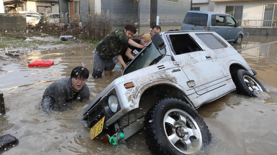 Residents try to upright a vehicle stuck in a flood hit area. The assessment of casualties has been difficult because of the widespread area affected. Officials in Ehime prefecture asked the central government to review a weather warning system, noting that rain warnings were issued after damage and casualties were occurring.  (JIJI Press / AFP)
