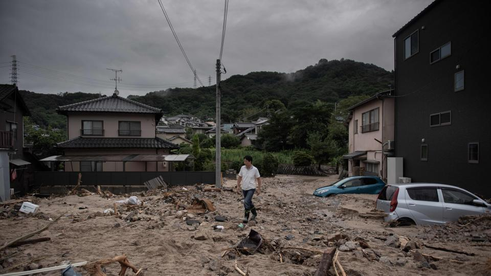 A man walks past a devastated street during floods in Saka. The government has set up a task force to speed up deliveries of supplies and other support for evacuation centers and residents in the region, but disrupted roads and other ground transportation have delayed shipment, raising concerns of shortages. (Martin Bureau / AFP)
