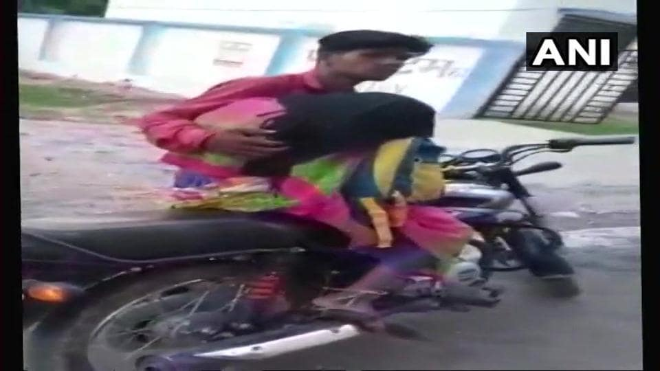 Man takes dead body of mother on a motorcycle for post mortem after being allegedly denied hearse van by district hospital in Mohangarh.