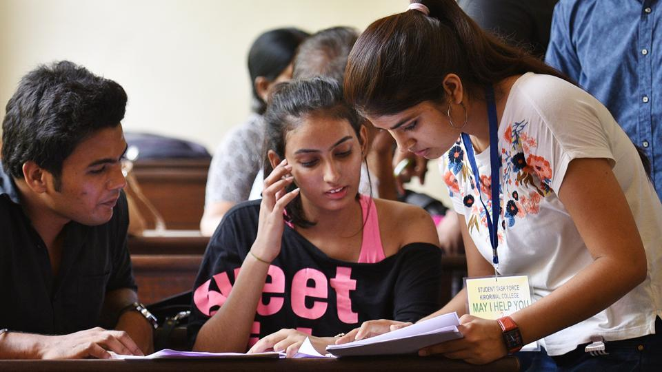 A volunteer helps Delhi University (DU) aspirants fill their admission forms for the new academic session 2018-19 at Kirori Mal College, in New Delhi on  June 25, 2018.