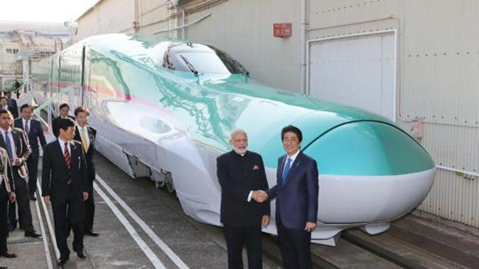 This file photo taken on November 12, 2016, shows Prime Minister Narendra Modi and his Japanese counterpart Shinzo Abe in front of a Shinkansen train during their inspection of a bullet train manufacturing plant in Kobe, Hyogo prefecture