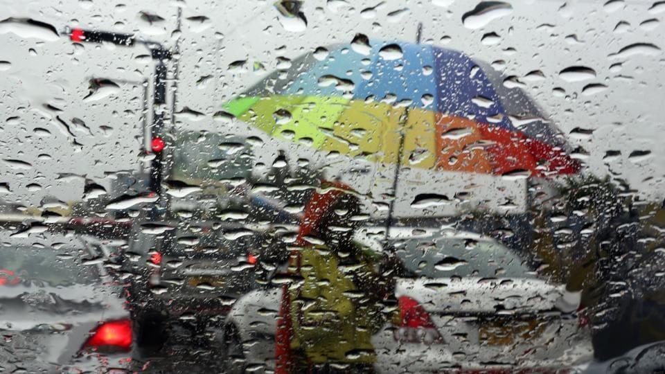 Rain drops are seen on the window of a car as a woman sells umbrellas at a traffic intersection in Hyderabad. Heavy to very heavy rain  is expected to hit isolated parts of Uttar Pradesh, Uttarakhand, east Rajasthan, Madhya Pradesh, coastal Andhra Pradesh, Telangana, coastal & south interior Karnataka and Kerala. (Mahesh Kumar A / AP)