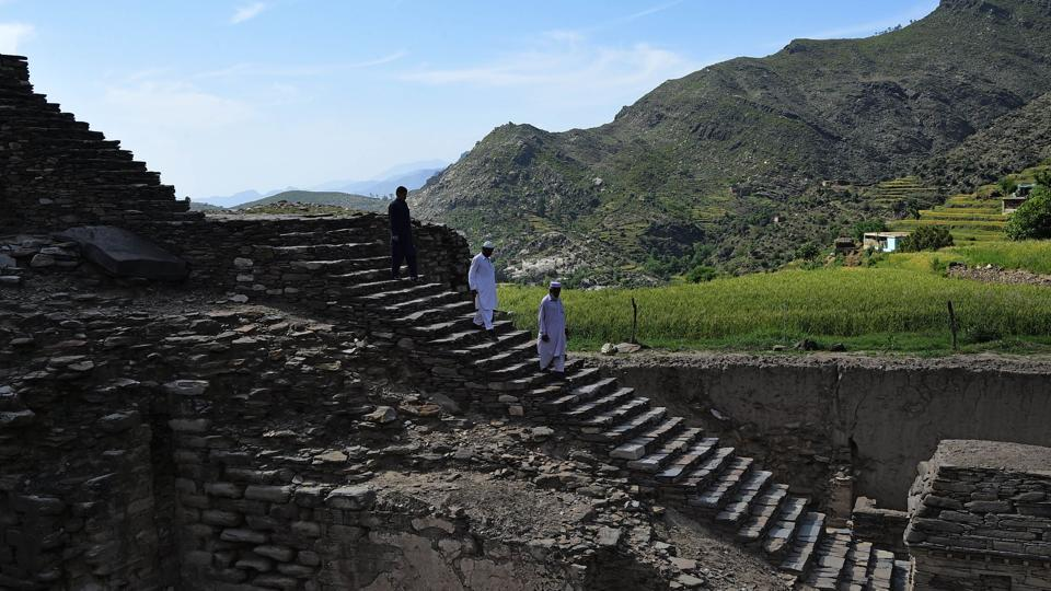 Visitors walk down stairs to see a centuries-old stupa. Buddhism for its part disappeared from the region around the 10th century AD, driven out by Islam and Hinduism. Its golden age in Swat lasted from the second to the fourth centuries, when more than 1,000 monasteries, sanctuaries and stupas spread out in constellations across the valley. (Abdul Majeed / AFP)