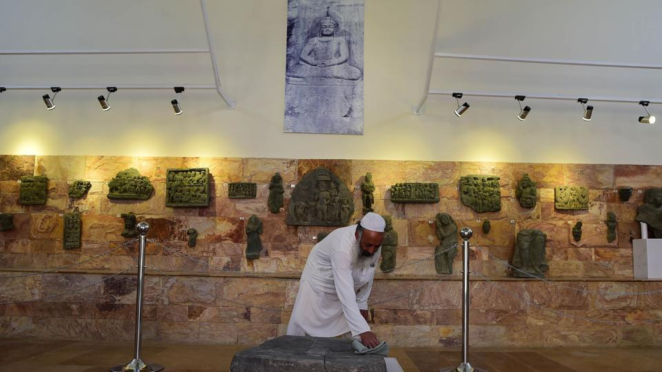 "A worker cleans a rock with images of Buddha's feet at the museum in Mingora. Fazal Khaliq, a journalist and author in Mingora, thinks the threat to cultural heritage has been ""minimised"" through education and the use of social networks to spread a ""soft, good"" image. The museum in Mingora now welcomes mullahs ""who like Buddhism"", says its curator, Faiz-ur-Rehman. ""Before Islam, this was our religion,"" he said. (Abdul Majeed / AFP)"