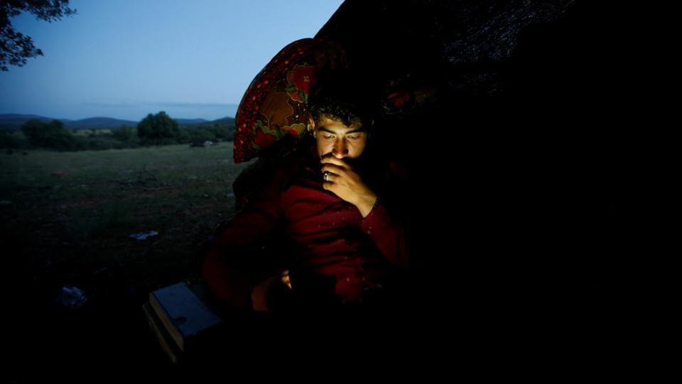 "Muhammet Gobut sits inside their tent while looking at his phone near Konya. ""I had a social life in college ... (and) I could go to the hospital whenever I needed to"", Gulay said. ""But none of these exist in the nomadic life. We are alone with nature."" (Osman Orsal / REUTERS)"