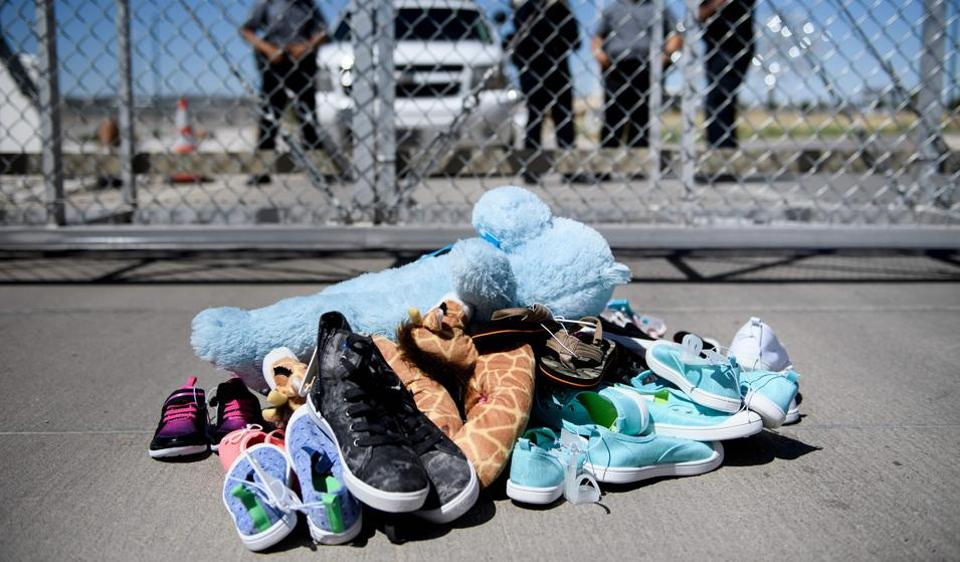 Security personal stand before shoes and toys left at the Tornillo Port of Entry in Tornillo, Texas, where minors crossing the border without proper papers have been housed after being separated from adults
