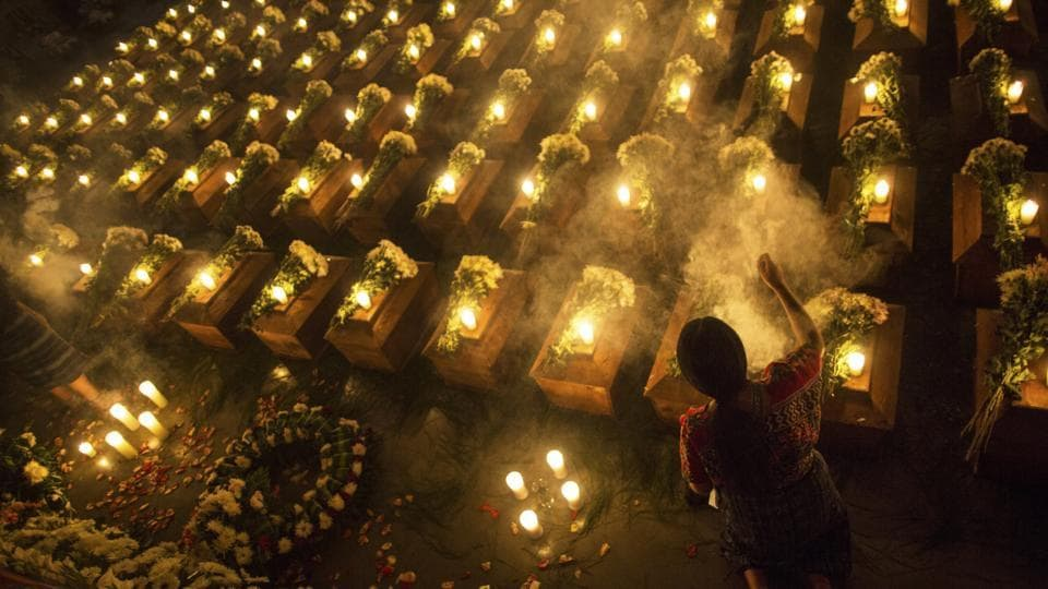 A woman spreads incense over coffins holding the remains of 172 unidentified people who were discovered buried at what once was a military camp in San Juan Comalapa, Guatemala, one day before their formal burial at the same site where they were discovered. (Rodrigo Abd / AP)