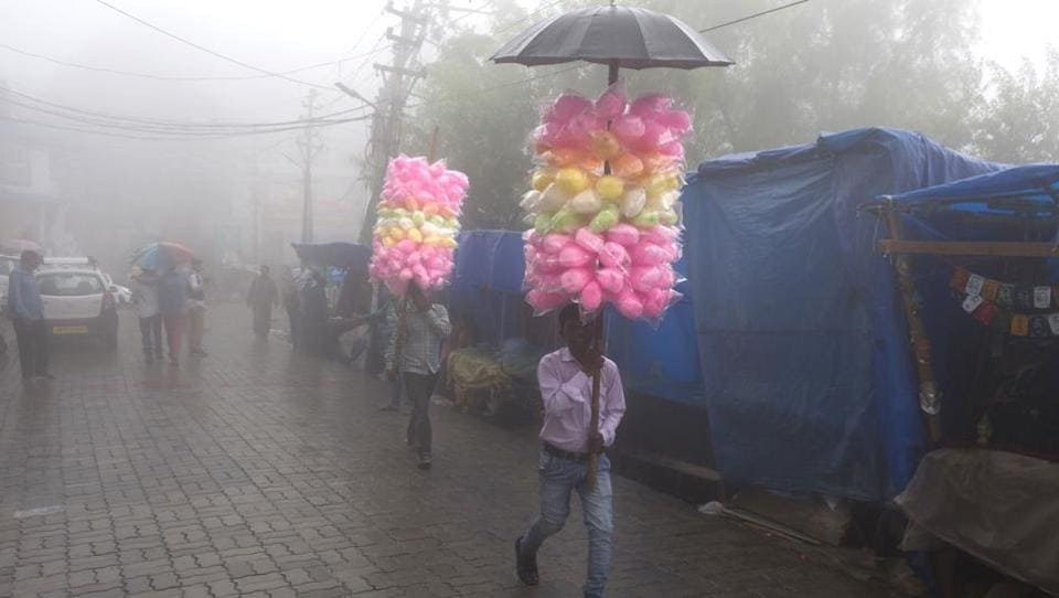 Travelling vendors selling cotton-candy walk amid fog in Dharmsala on July 9, 2018. (Ashwini Bhatia / AP)