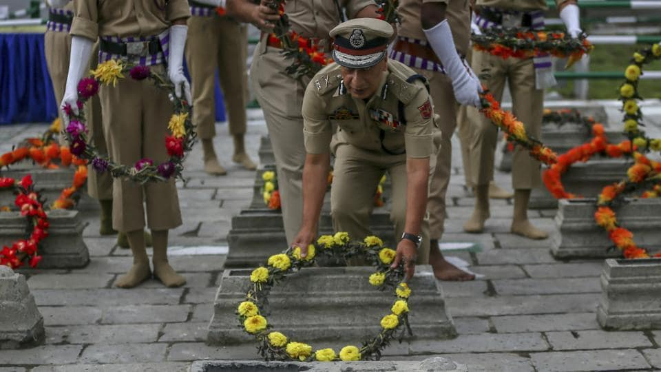 A police officer lays a wreath on a grave at Martyrs' Graveyard in Srinagar. July 13 is observed as Martyrs' Day in memory of the day when the region's Hindu king ordered the execution of more than 20 Kashmiri Muslims in a bid to put down an uprising in 1931. (Dar Yasin / AP)