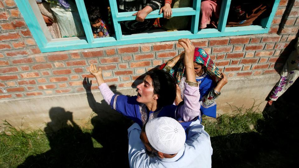 A man tries to console a woman as she watches the body of Tamsheel Ahmad Khan, a civilian who according to local media died during clashes between protesters and Indian security forces, during his funeral at Vehil village in Kashmir's Shopian district on July 10, 2018. (Danish Ismail / REUTERS)