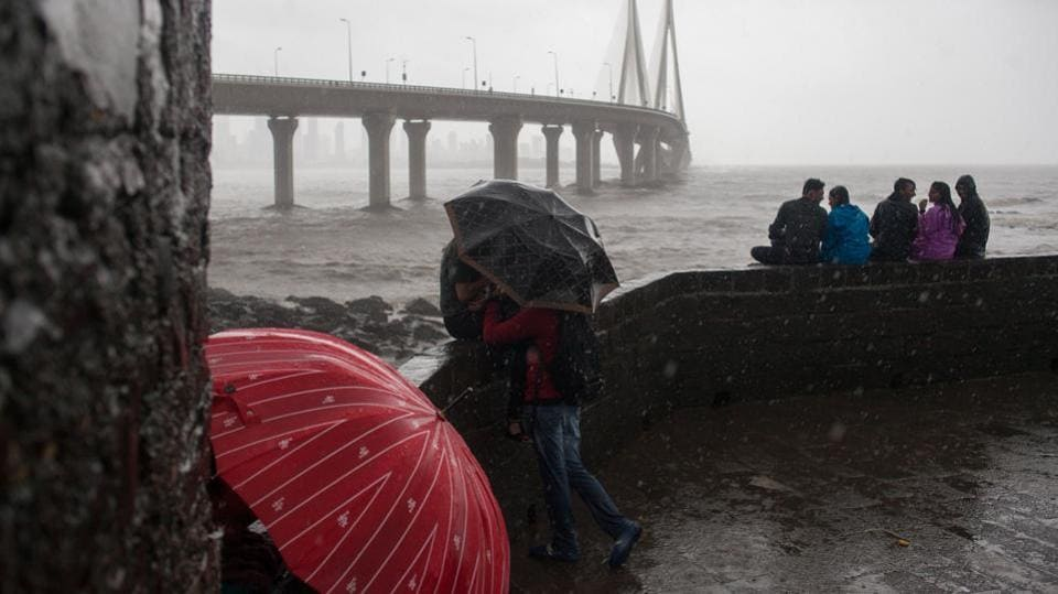 People use umbrellas to shield themselves from the rain as the Bandra-World Sea Link bridge stands in the background in the suburb of Bandra in Mumbai on July 10, 2018. (Karen Dias / Bloomberg)