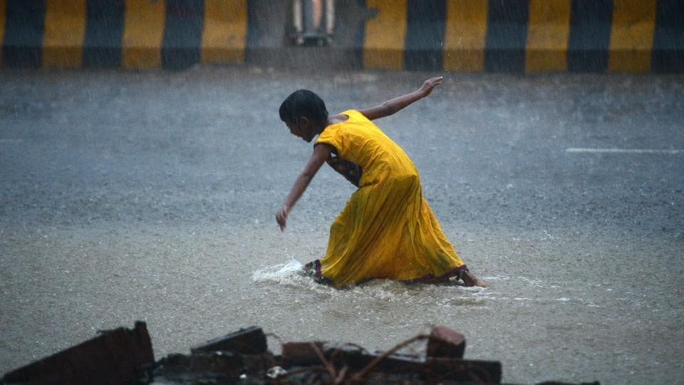 A girl walks on a road during heavy rain showers in Allahabad on July 11, 2018. (Sanjay Kanojia / AFP)