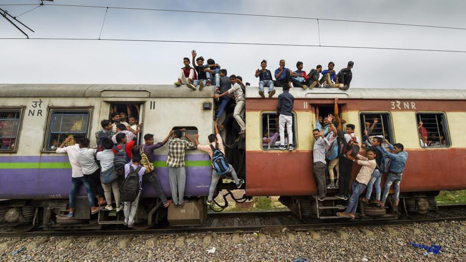 Commuters hang on the gates and sit on the roof while travelling by a crowded train on World Population Day at Noli Railway Station near Ghaziabad on July 11, 2018. (PTI)