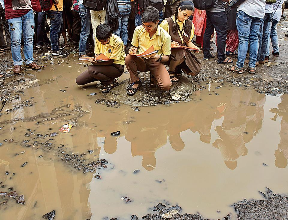 Students of Sane Guruji School paint potholes in Santacruz on Saturday, as part of an agitation against the government's indifference towards the condition of Mumbai's roads.