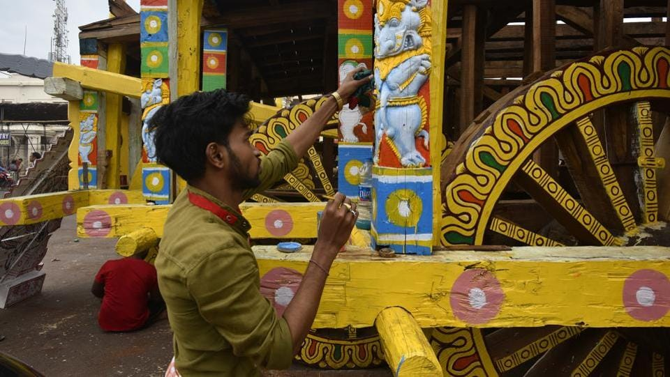 An artist paints a part of the chariot  ahead of the Rath Yatra.  While new chariots are made every year, the wooden horses and charioteers for each rath and the smaller deities that adorn the chariots, are made once in approximately 12 years, when the wooden idols of Jagannath and his siblings that are worshipped in the temple are replaced. That ritual – referred to as Navakalebara or new-body ceremony – was last celebrated in 2015. (Raj K Raj / HT Photo)