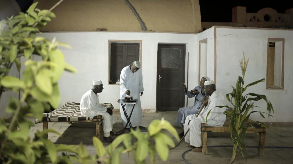 Men talk at a home in Wadi Karkar, a new complex under construction in the desert west of Lake Nasser.  In the decades since, Nubian towns — like many others in southern Egypt — have sunk into poverty. Many Nubians have moved to larger cities like Cairo, Alexandria or Aswan, searching for jobs. Customs have withered. The Nubian language is not taught in schools. (Nariman El-Mofty / AP)