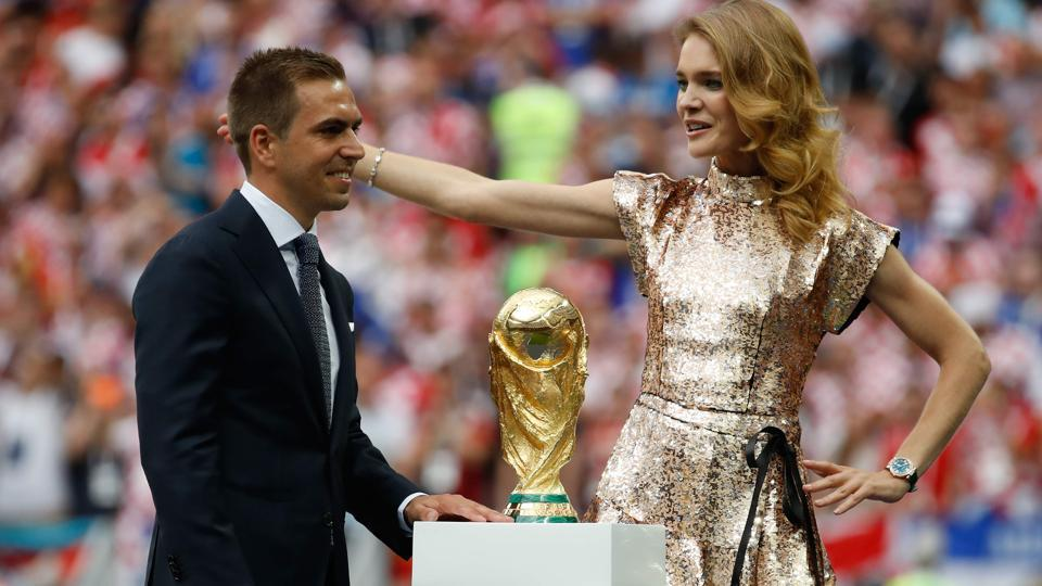 Germany's former captain Philipp Lahm (L) presents the trophy with Russian model Natalia Vodianova during the closing ceremony prior to the Russia 2018 World Cup final football match between France and Croatia. (AFP)