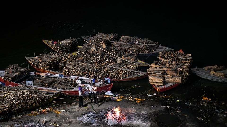 "People wait for a dead body to finish being cremated at the Manikarnika ghat. ""Times may change but nothing will change here. People will keep dying and coming to Varanasi, and will look to the Doms to do the sacred work of the gods,"" Choudhury said. (Chandan Khanna / AFP)"