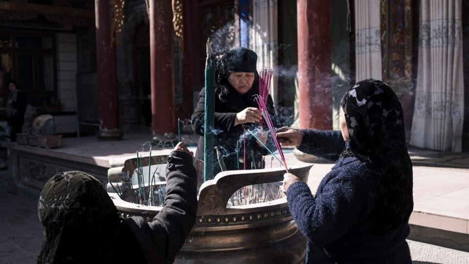 "Ethnic Hui Muslim women praying in a courtyard at a religious site in Linxia. Women in headscarves dish out boiled lamb in mirror-panelled halal eateries while streams of white-hatted men meander into mosques for afternoon prayers, passing shops hawking rugs, incense and ""eight treasure tea,"" a local speciality including dates and dried chrysanthemum buds. (Johannes Eisele / AFP)"