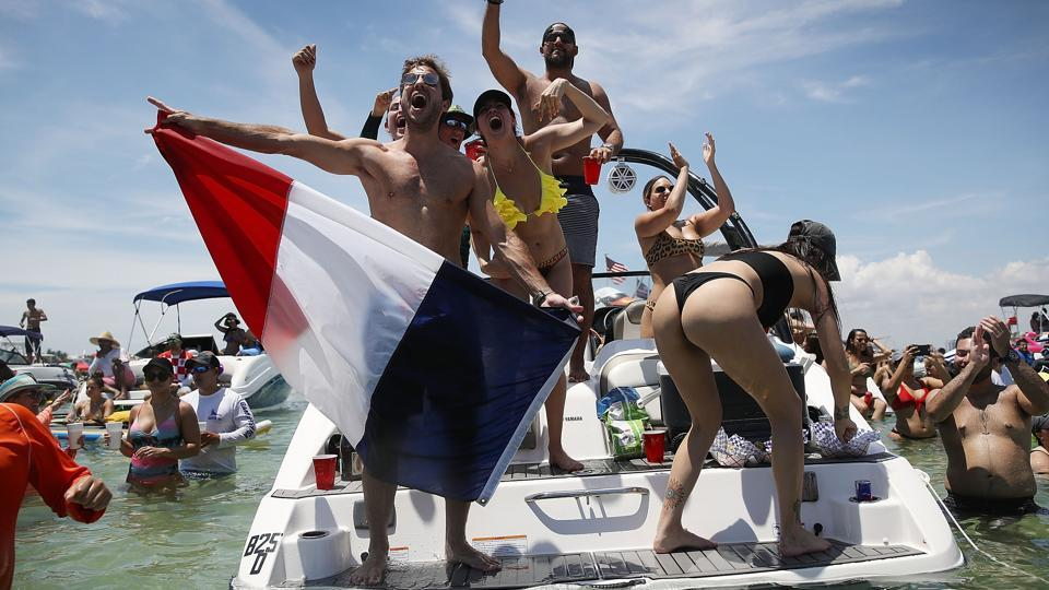 People react to France scoring their 4th goal against Croatia in the World Cup final as it is being broadcast from the Ballyhoo Media boat setup in the Intracoastal Waterway on July 15, 2018 in Miami Beach, Florida. (AFP)