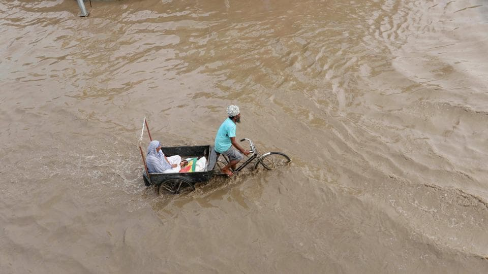 A rickshaw-puller carries an elderly woman through a flooded street after rains in Patiala, Punjab. Also, rail and road traffic were hit in various parts of Kerala due to waterlogging as heavy rains continued to pound the state with the South West Monsoon becoming active again. (PTI)