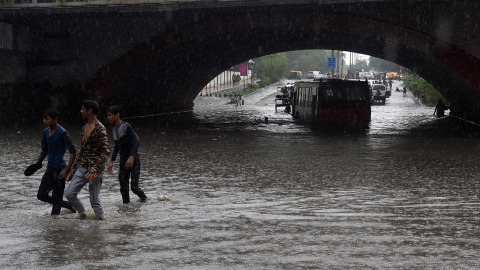A bus is seen submerged under Minto bridge as Indian youths walk along a water-logged road during heavy monsoon rain in New Delhi on July 16.
