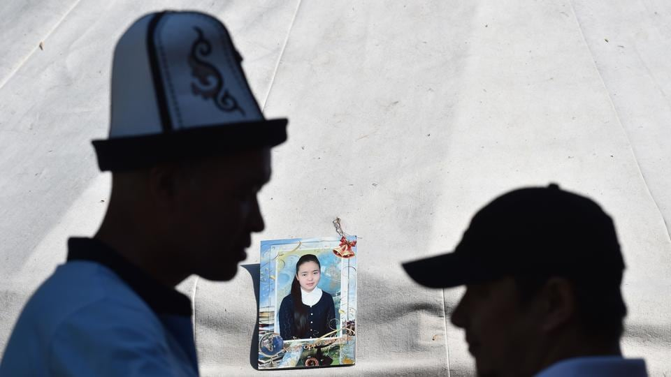 """A photo frame of Burulai Turdaaly Kyzy, a 20-year-old medical student seen outside a tent during a traditional ceremony to mark 40 days since she was murdered in a police station by her kidnapper, at a nomadic yurt pitched next to her family home in the settlement of Sokuluk, northern Kyrgyzstan. """"She was my youngest daughter. Humble and well-behaved,"""" the victim's mother, Gulnara Kozhanaliyeva said through tears. (Vyacheslav OSELEDKO / AFP)"""