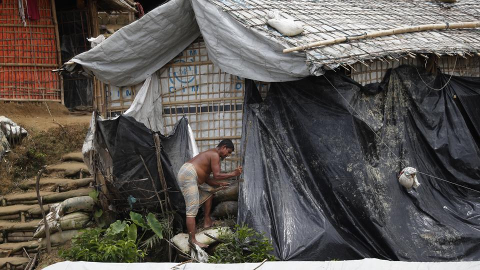 A man covers his shelter with waterproof tarp in Chakmarkul refugee camp. The most intense rains are expected over the next few months, though downpours began pummeling the camps in June. There have already been more than 160 landslides, 30 people injured and one toddler killed, according to the Inter Sector Coordination Group, or ISCG, which oversees aid agencies in the camps. (Wong Maye-E / AP)